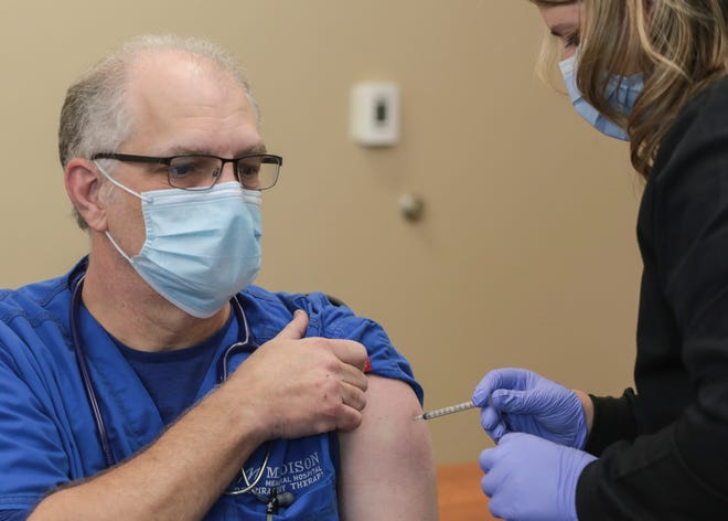 Danny Wilson, a respiratory therapist, receives a dose of the Pfizer-BioNTech vaccine for COVID-19 at Madison Memorial Hospital in Rexburg, Idaho on Monday.