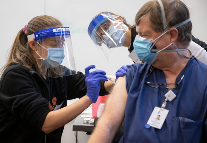 Nursing student Abriana Martinez administers the Pfizer coronavirus vaccine to Dr. Erik Pronske at the University of Texas Health Austin Dell Medical School on Tuesday December 15, 2020.  UT School of Nursing faculty member Alexandra Garcia watches.