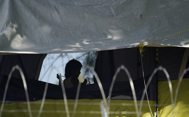 A young girl plays in her family's tent at a camp of asylum seekers stuck at America's doorstep last month in Matamoros, Tamaulipas. Increasing numbers of parents and children are crossing the border, driven by violence and poverty in Central America and growing desperation in migrant camps in Mexico.