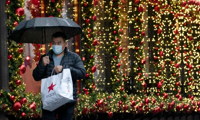 A shopper walks past a store's holiday window display in New York on Nov. 30. While shoppers are planning to spend less this year than last, according to a NerdWallet survey, more are also planning to use credit cards to purchase gifts.