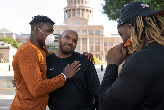 University of Texas football Player Development Director Kevin Washington, middle, hugs Longhorn players after Washington gave an impassioned speech at the end of team's march to the Capitol on June 4.