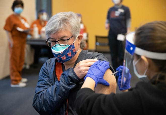 Nursing student Abriana Martinez administers the Pfizer coronavirus vaccine Dec. 15 to Dr. Andrew Reifsnyder at the University of Texas Dell Medical School.