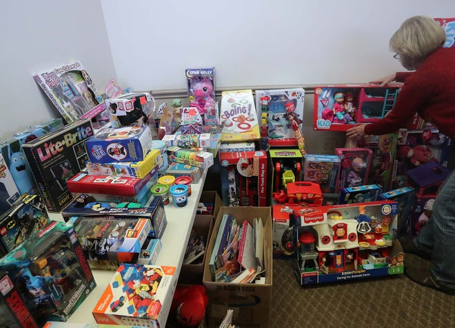 Mary Fair, a volunteer with Cuyahoga Falls Good Neighbors, arranges donated toys Dec. 15 to be given to families in need as Cuyahoga Falls Good Neighbors hosts a Christmas drive-thru program where they provide food, clothing and gifts for families in need.