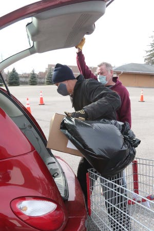 Cuyahoga Falls firefighter Eddie McCullough, front, and retired firefighter Dave Reifsnyder volunteer with Cuyahoga Falls Good Neighbors as they load a person's car Dec. 15 with food, during a Good Neighbors drive-thru program. [Karen Schiely/Beacon Journal]