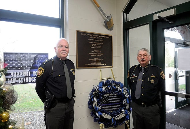 Ashland County Sheriff Jail Administrator Capt. Dave Blake, left, and Sheriff E. Wayne Risner pose on Tuesday, Dec. 15 next to the dedication plaque in the lobby of the County Jail that is celebrating its 20th anniversary.