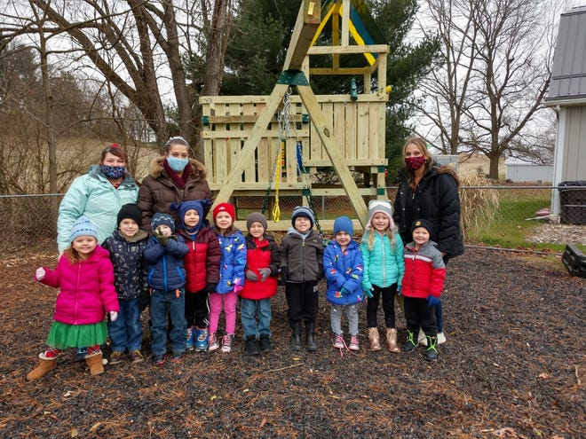 Students and teachers at the Kno-Ho-Co Head Start daycare in Loudonville pose in front of the new playground gym set built at their facility earlier this month. A $2,500 grant from the Home Depot Foundation, through the Ashland store, funded the project, with the Ashland County-West Holmes Career Center construction class building it.