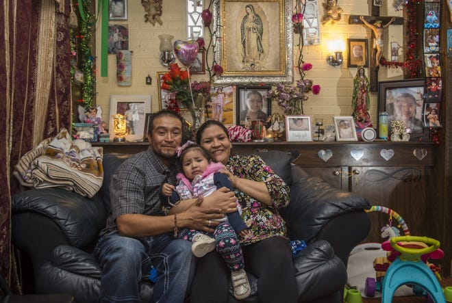 Sarahi and her husband, Cuahutemoc, hold their 1-year-old daughter, Yaretzi, in their living room near Augusta. Sarahi has received care from Clinica Latina, which serves the underserved, uninsured and undocumented in the Augusta area.