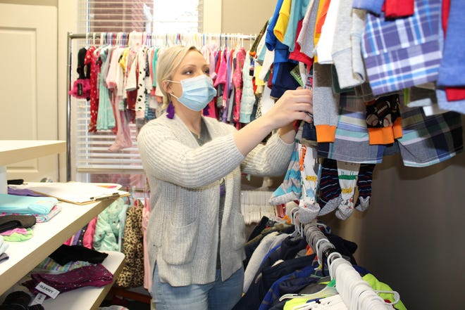Ray of Hope case manager Shelbi Vik sorts through baby apparel in the agency's clothes closet.