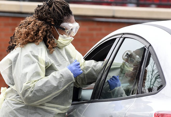 Boone Hospital Center registered nurse Phyliss Golden performs a nasopharyngeal swab on a drive-thru patient last year at Boone Hospital Center.