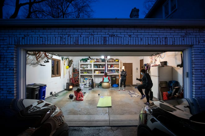 Maria Stavridis, 21, left, her mother Olga Stavridis, 53, and Donna Reda, 70, right, work out with personal trainer Caitlin Kennelly of Columbus Fitness Consultants before sunrise in the garage of Reda's Upper Arlington home. Experts agree that home workouts can be effective during the COVID-19 pandemic at little cost.