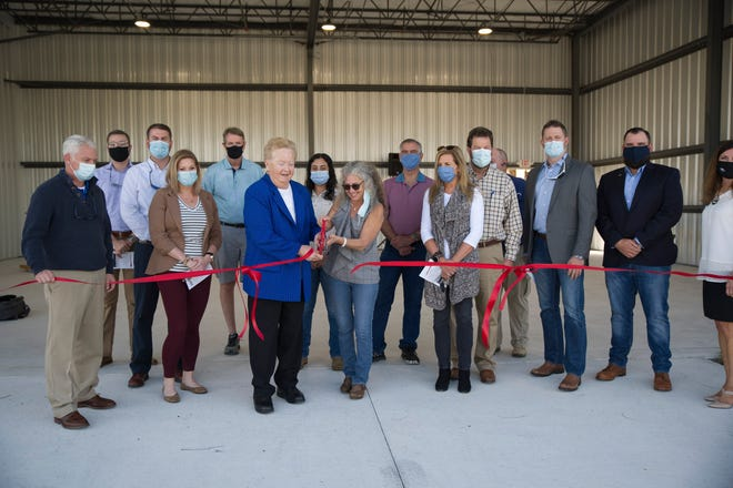 Leesburg Mayor Elise Dennison and Aiport Manager Tracey Dean cut the ribbon for the new hangars at the Leesburg International Airport on Tuesday. [Cindy Peterson/Correspondent]