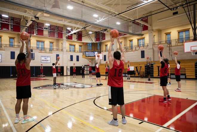 Players stand six feet apart during warm ups in the gymnasium for boys basketball tryouts at Whitman-Hanson Regional High School on Monday, Dec. 14, 2020.