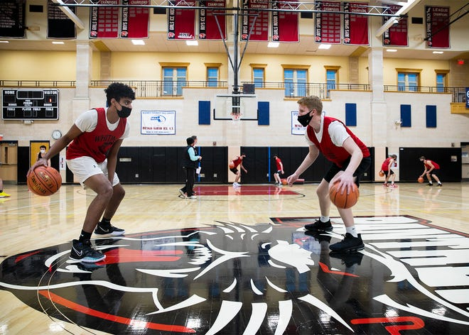 Whitman-Hanson Regional High School varsity basketball returning stars Nate Amado and Cole LeVangie mime each other dribbling during tryouts in the gymnasium on Monday, Dec. 14, 2020.