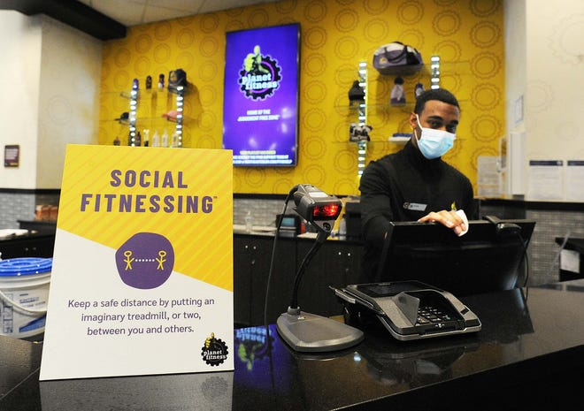 Employee Tyler White sanitizes a computer at Planet Fitness at the Westgate Mall, Tuesday, Dec. 15, 2020.  Fitness and health centers, including gyms, had to close in Brockton as of Dec. 16 after the mayor voluntarily decided to revert to Step 2 of Phase 2 in the state's reopening plan.