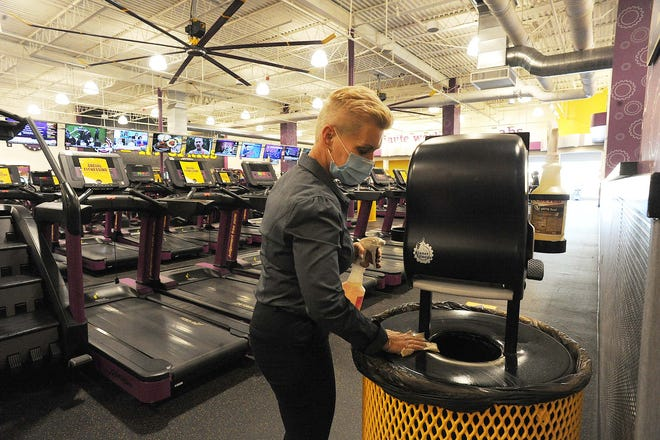 Tracy Waters, a regional manager at Planet Fitness, sanitizes a paper towel dispenser and trash can at the gym, which is located at the Westgate Mall in Brockton, Tuesday, Dec. 15, 2020. Gyms are one industry that has to close effective Wednesday in the city due to a voluntary rollback to Step 2 or Phase 2 in the state's reopening plan.
