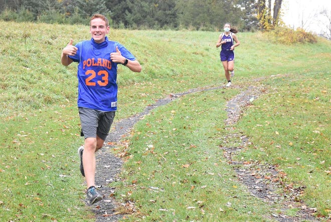 Poland senior Chris Gauthier gives spectators two thumbs up as he leads his first varsity cross country race Oct. 24 in Little Falls. In the background is Little Falls' Kaylan Zysk who won the girls' race.