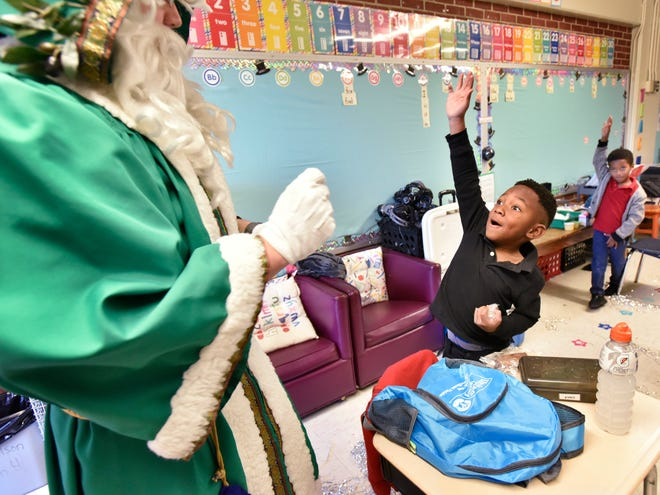 """In 2019, Saint Nicholas, played by Bailey Bird, talks with kindergartner Kyro Mahone, 5, during a visit to Parkwood Heights Elementary School in Jacksonville. The visit was part of the United Way of Northeast Florida's 17th annual """"Discovery Day"""" at six Title 1 Duval County public schools."""
