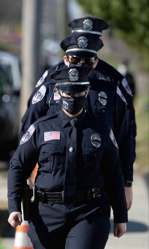 A trio of Shelby officers make their way to the First Baptist Church Worship Center after parking their patrol cars on West Mountain Street on Tuesday, Dec. 15, 2020.