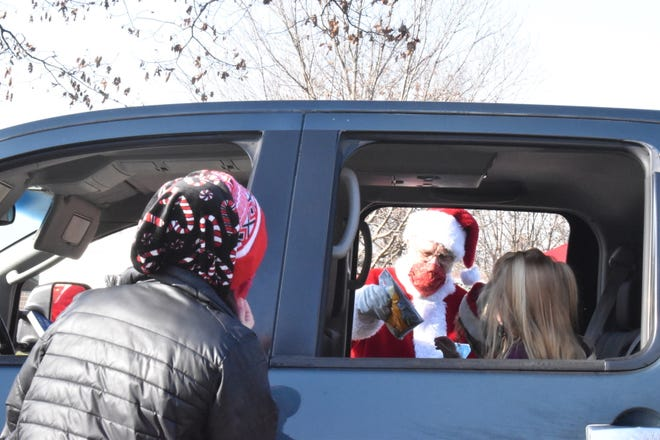 Main Street Orion hosted a drive-through Saturday with Santa on Dec. 5 at Central Park, Orion. In this photo, Santa hands a goodie bag through a rolled-down window, while Executive Director Kassi Clear, left, watches. Max McCaw arranged Santa's visit, which saw the special guest handing out 284 goodie bags