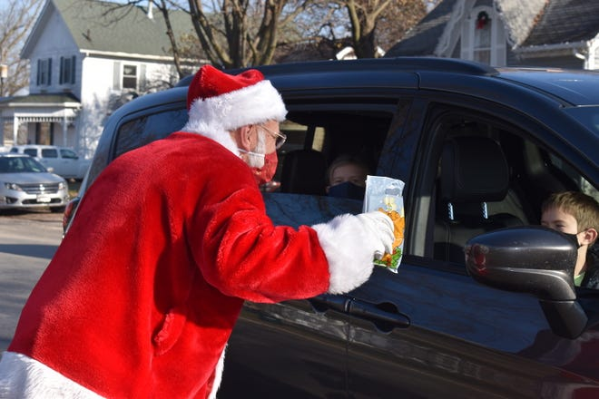Santa leans into a van to talk to two children during Main Street Orion's Saturday with Santa on Dec. 5 at Central Park. Max McCaw provided for Santa's visit. Main Street Orion volunteers created 300 goodie bags, with only 16 left over when the event ended.