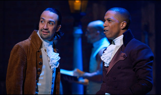 """This image released by Disney+ shows Lin-Manuel Miranda, left, and Leslie Odom Jr. during a performance of """"Hamilton.""""  When Hamilton debuted on the new Disney + streaming service before its intended 2021 theater release, it was more than a harbinger for other big-screen films during the pandemic. It demonstrated how critical streaming platforms are to the fortunes of their parent companies, as NBCUniversal's Peacock and WarnerMedia's HBO Max. (Disney+ via AP)"""