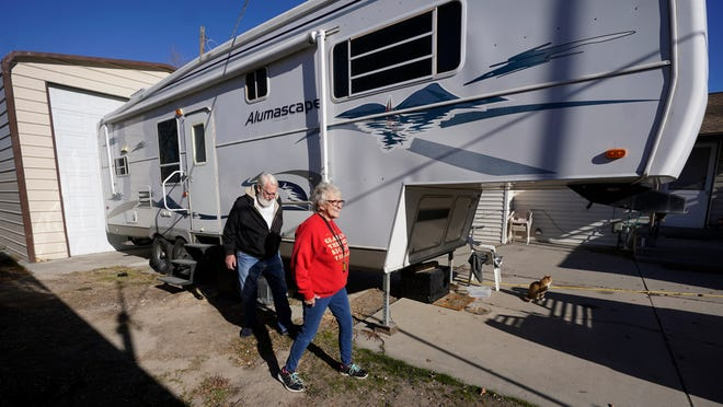 Kathy and Bud Scott walk past their fifth wheel travel trailer at their home Thursday, Dec. 3, 2020, in West Valley, Utah. Many snowbirds who live part time in warmer climates to escape cold weather won't be flocking south this winter. (AP Photo/Rick Bowmer)