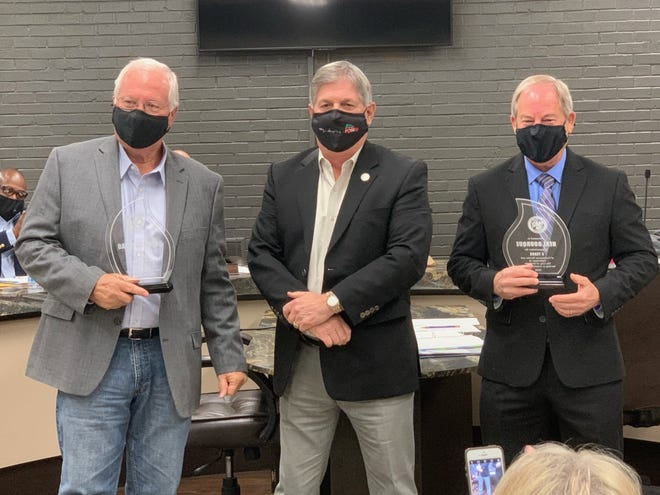 Gonzales Mayor Barney Arceneaux, center, presents plaques to outgoing city councilmen David Guitreau, left, and Neal Bourque, right, commemorating their service on the council.