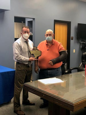Grayson County District Attorney Brett Smith, left, presents an award to retiring Domestic Violence Investigator Terry Dunn recently.