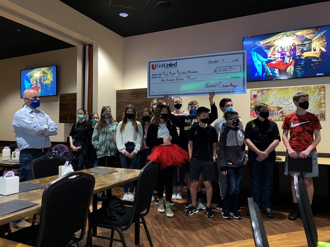 Students celebrate the success of a recent hot chocolate fundraiser at HeyDay in Denison last week. Four teams of students raised more than $10,000 in support of the Red River Railroad Museum as a part of Denison's annual Christmas parade festivities.