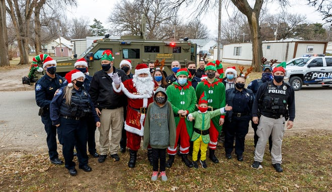 Members of the Reno County Sheriff's Department and officers with multiple other rural police departments in the county delivered gifts to more than 30 children Saturday. [Photo courtesy Nick Hemphill]