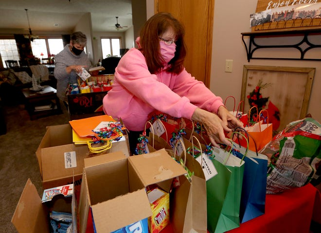Barbara Allen picks up filled bags while Debra Esau puts hand written Christmas card notes into other bags Tuesday afternoon. These Serendipity Class members, Allen, Esau, Peggy Schmidt put together the gift bags. Barbara Gillaspie also helped by shopping for supplies.