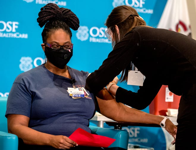 Chemica Jones, a CNA at OSF HealthCare St. Francis Medical Center, keeps her eyes closed as RN Shannon Lesch administers a dose of the Pfizer COVID-19 vaccine Tuesday, Dec. 15, 2020 at Jump Trading Simulation and Education Center in Peoria. Jones was the first of five volunteers to receive the vaccine.