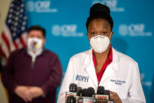Dr. Ngozi Ezike of the Illinois Department of Public Health answers questions during a press conference Dec. 15 at OSF HealthCare Jump Trading and Simulation Center in Peoria. In the background is Gov. J.B. Pritzker. Five medical workers were inoculated with the first dose of the Pfizer COVID-19 vaccine.