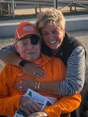 Suzy Thompson hugs Hugh Dunn prior to a football game in Macon.