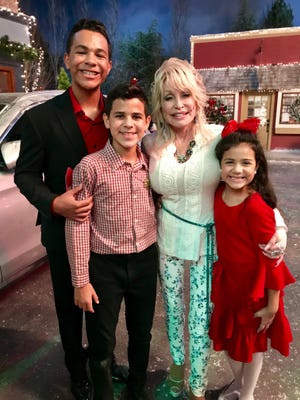 "Dolly Parton poses with the Hill siblings, from left, Tristan, Tyson and Talia, on the set of ""Christmas on the Square"" in Atlanta. The Davenport siblings were all cast in the movie, shot last year and now streaming on Netflix."