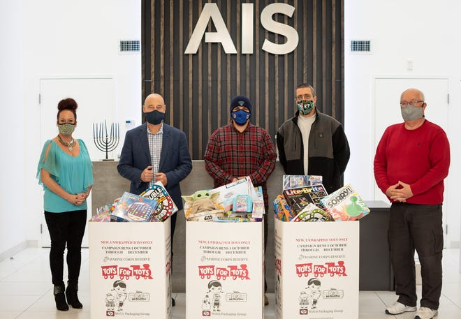 From left, Elena Goudey and Bruce Platzman from AIS, Tyler and Jeff Yalian on behalf of Christmas on Tolman Ave., and Rick Marchand from AIS.