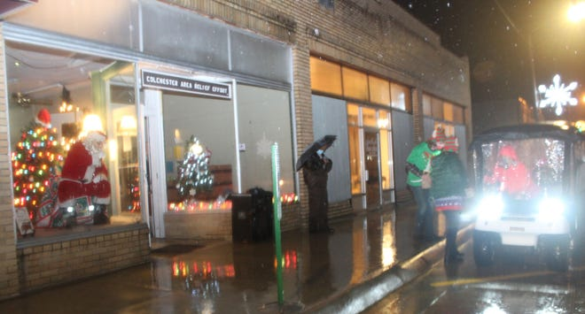 Santa sits in the Colchester Area Relief Effort window while visitors drive up in the rain to drop off letters and say hello to Santa.