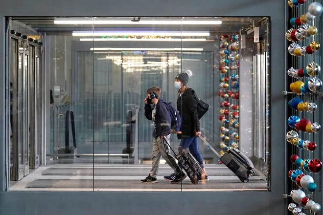 In this Nov. 29, 2020, file photo, travelers walk through Terminal 3 at O'Hare International Airport in Chicago. With some Americans now paying the price for what they did over Thanksgiving, health officials are warning people — begging them, even — not to make the same mistake during the Christmas and New Year's season. (AP Photo/Nam Y. Huh, File)