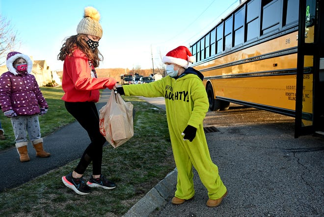 Albie Lomberto, 10, right, takes a food donation from Mia Santomenna, 10, as Abigail Stover, 7, looks on,  in the Roland Way neighborhood of Milford, as part of a unique food drive for the schools' free breakfast and lunch program, Tuesday, Dec. 15. Instead of picking up students, who have been taking classes remotely since Nov. 23, the buses made their rounds picking up food donations.