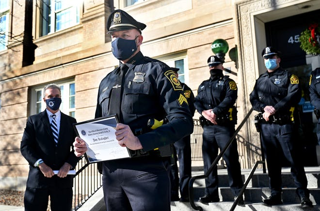 Westboro Police Sgt. Jon Kalagher, center, accepts a certificate from Worcester County District Attorney Joseph Early, left, during a ceremony honoring Sgt. Kalagher for saving a stabbing victim's life last year.