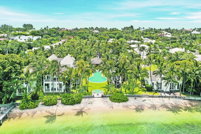 Viewed from the Intracoastal Waterway, this Bermuda-style estate at 1480 N. Lake Way on the North End of Palm Beach comprises the main house on the left, a poolside cabana and a guesthouse on the right.