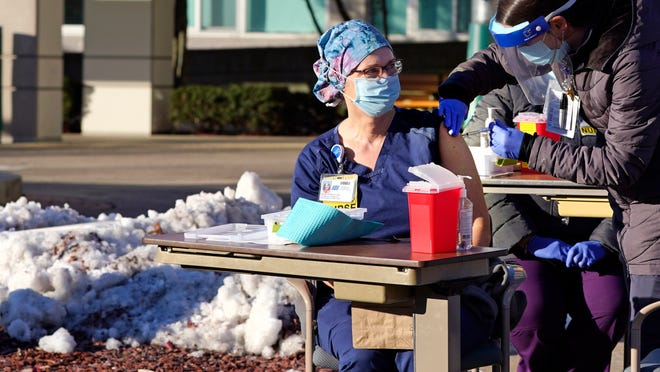 With temperatures slightly below freezing, intensive care unit nurse Heidi Kukla, center, sits next to a snow bank as she is injected with the Pfizer-BioNTech COVID-19 vaccine outside the Elliot Hospital, Tuesday, Dec. 15, 2020, in Manchester, N.H.