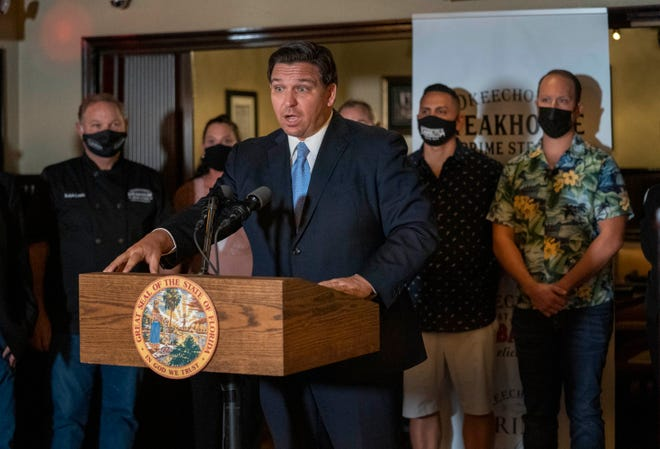 Florida Gov. Ron DeSantis speaks during a news conference Tuesday at the Okeechobee Steakhouse in West Palm Beach. DeSantis talked about the importance of keeping restaurants open during the pandemic to help employees earn a living. (GREG LOVETT/THE PALM BEACH POST)