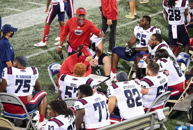 FAU coach Willie Taggart, standing and talking to the offensive line during the Owls' win against FIU in the Shula Bowl last month, hopes the commitments hold up during the early signing period.