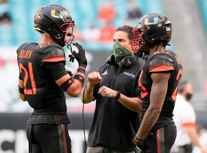 Miami Hurricanes coach Manny Diaz talks with safety Bubba Bolden (21) during Saturday's 62-26 loss to North Carolina at Hard Rock Stadium.