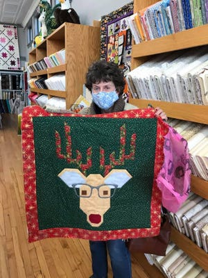 Peggy Stanfield of Wellington shows her recently completed reindeer quilt, made with supplies from the Beehive Quilt Shop and Bee Creative Toys store in Wellington.