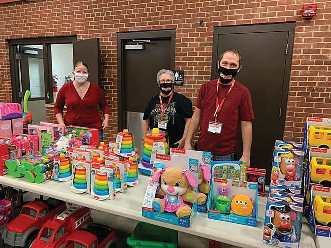 Community volunteers (from left) Wysdom Zerba, Autumn Wittig and Brent Wittig joined others in helping distribute donated toys to children from Pratt, Kingman and Kiowa counties last Saturday at the Pratt Armory.