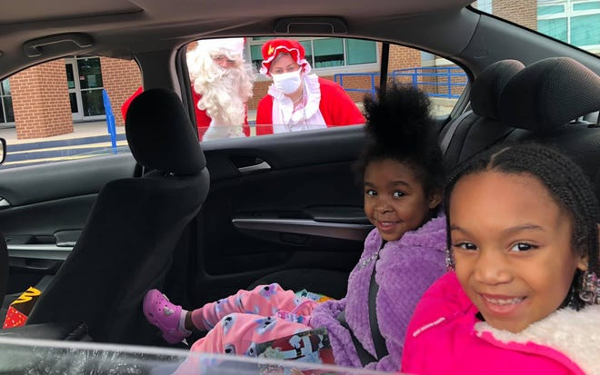 From left to right, six-year-old friends Nilah Chambers of Hopewell and Alana Williams of Petersburg visit Mr. and Mrs. Claus in Hopewell at the high school on Dec. 12, 2020.