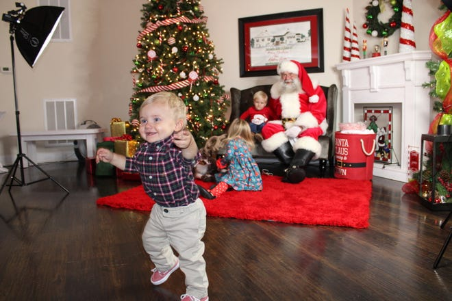 One-year-old Isaac Anderson runs away from Santa during a photo session at Adaline Acres in Chester on Dec. 5, 2020. Also pictured are Isaac's cousins Rylee and Zeke Sites.