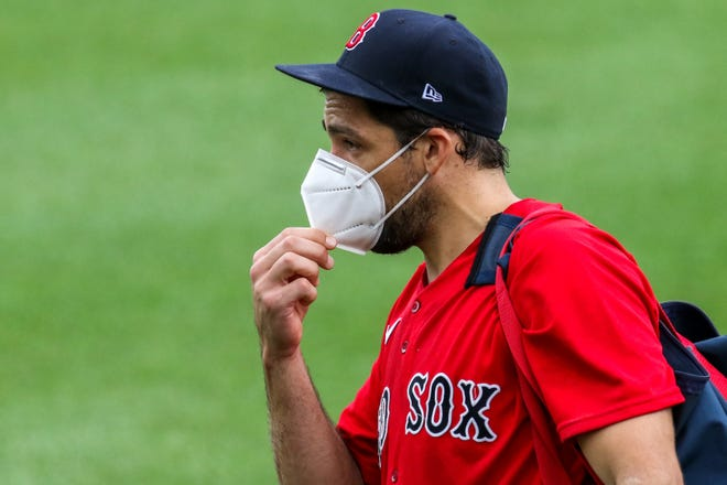 Red Sox starting pitcher Nathan Eovaldi adjusts his mask during Summer Camp practice at Fenway Park in July.